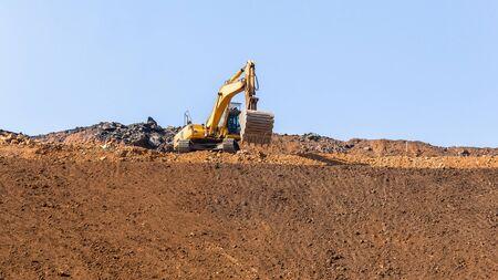 Industrial construction earthworks excavator machine on side of new raw earth sandbank platform against blue sky.
