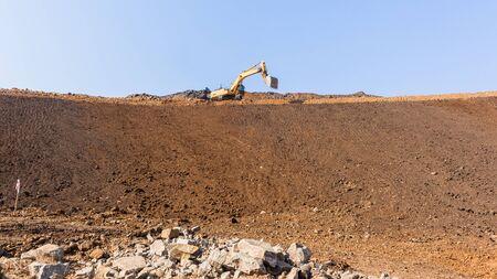 Industrial construction earthworks excavator machine on side of new raw earth sandbank  platform against blue sky. Фото со стока