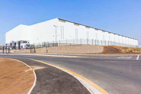 New warehouse factory building structure for business constructed roof covering off white panels and new roads outdoors blue skys.