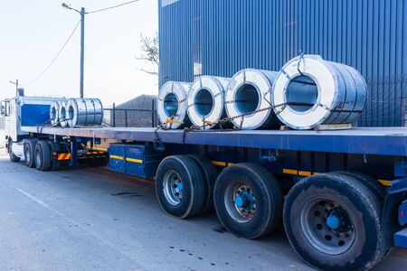 Truck transporting heavy steel sheet rolls secured on trailer from refinery to warehouse for customer manufacturing. 写真素材