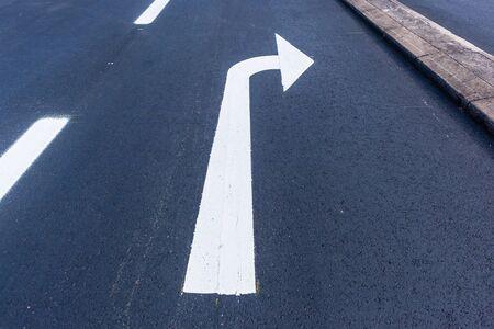 Straßen-Autobahn-Asphalt-Asphalt gemalte Richtungsmarkierung des weißen Pfeilzeichens für rechtsabbiegendes Verkehrsfahrzeugrouten-Overhead-Nahaufnahmefoto.