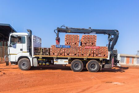 New red clay bricks blocks lifted by crane onto truck vehicle and trailer for delivery at construction building site in morning blue sky.