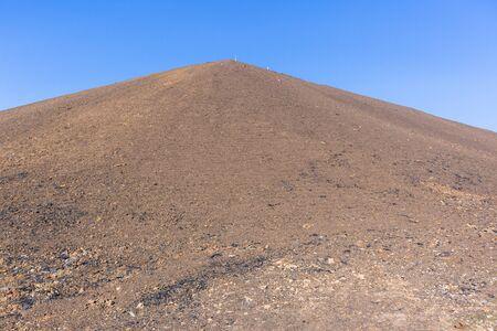 High brown sand texture steep embankment platform constuction excavation landscaping earthworks upwards with blue sky.