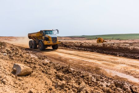 Industrial construction dump truck tipper bin moves earth on new industrial property earthworks development plateau expansion in countryside landscape. Stock Photo