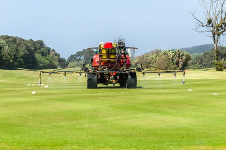 Golf course hole machine operator spraying treatment on grass putting green with surrounding trees coastal landscape. .