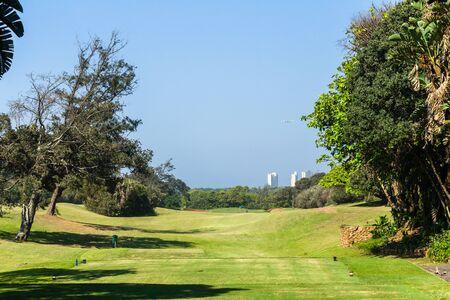 Golf course par four hole  number one coastal landscape short but narrow fairway sand traps trees slopes. 版權商用圖片