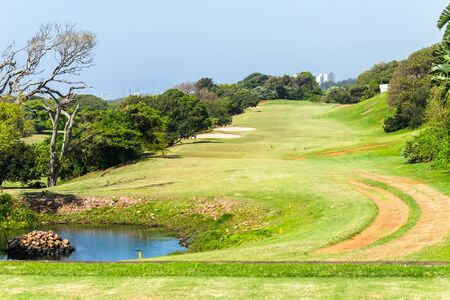 Golf course par 5 hole coastal landscape short but narrow fairway sand traps trees embankment for missed tee shots.