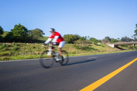 Cyclist riding on the road closeup motion speed blur cycling public race.