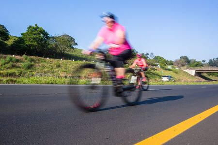 Cyclists riding on the road closeup motion speed blur cycling public race.