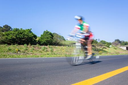 Cyclist riding on the road highway closeup motion speed blur cycling public race. Stock fotó