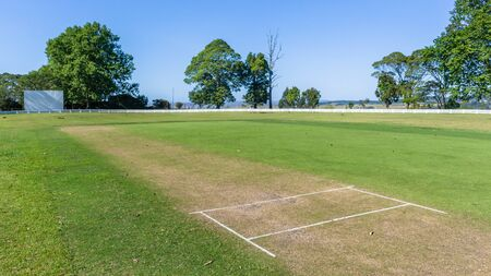 Scenic cricket grounds grass pitch white boundary fence of grass field summer blue day countryside landscape.