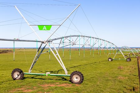 Farming farm irrigation equipment with line of steel pipe mobile water sprinklers on wheels for irrigation on food vegetable crops across fields.