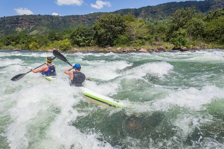Men athletes double pairs in canoe race rear action photo of  river rocks rapids with paddlers going through rushing rough waters.