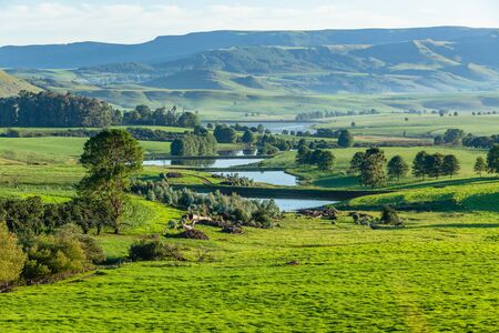 Scenic summer mountain farmlands with water catchment dams down the green landscape terrain.