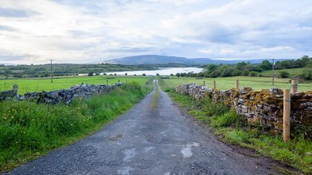 Rural road route farm countryside  scenic panoramic perspective toward lough lake landscape in North West Ireland. Banque d'images - 140990776