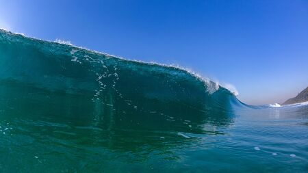 Ocean sea wave hollow tubing wall of water photo panoramic blue landscape.