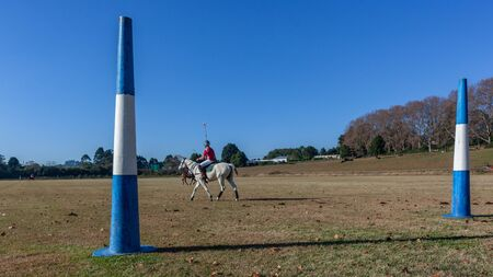 Polo riders players on field closeup goals blue sky a panoramic landscape photo.