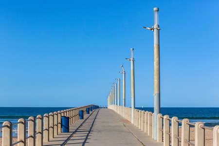 Beach pier walking concrete structure jetty with no people nobody empty towards blue ocean horizon . Standard-Bild