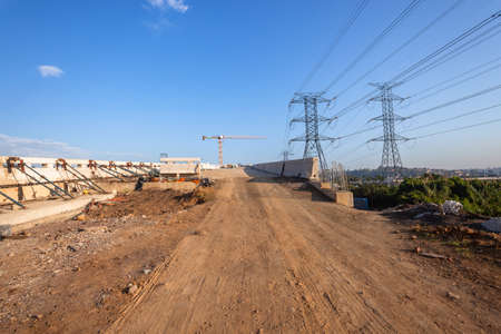 Construction of new civil engineering vehicle highway junction cross-over intersection concrete columns and off on ramps in morning blue sky