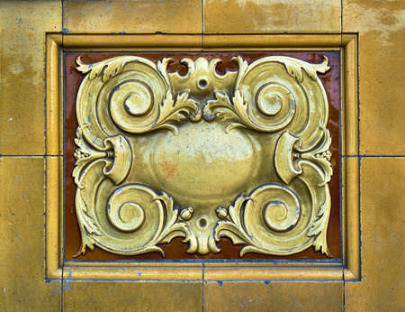 Detail of elaborate and decorative ceramic tiles in yellow gold and warm brown