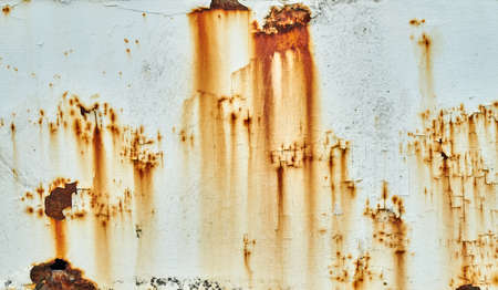 Patches of rust and peeling paint on a white wall