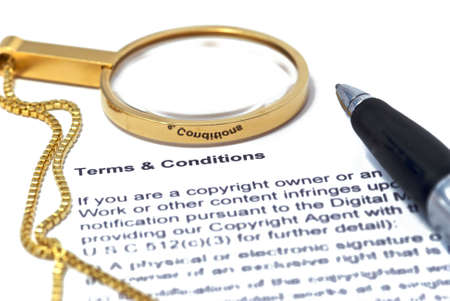 contracts: Terms and Conditions with magnifier and pen.