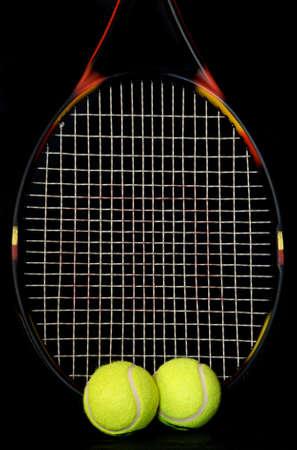 raquet: Tennis raquet and tennis balls on a black background.