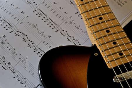 Electric guitar shown next to sheet music. photo