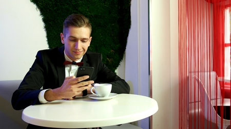 Young man using smartphone in a cafe