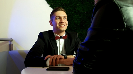 A young man on a date at the Cafe looks at his love girl Standard-Bild