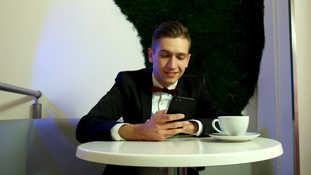 Young man in a black suit using a smartphone Standard-Bild