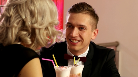 Young guy in a black jacket on a date in the Café