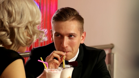 Young man on a date is drinking milk cocktail