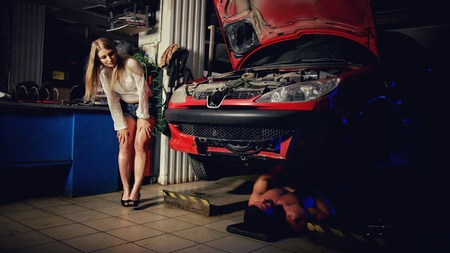 Girl in the garage watching as master man repairs his car 스톡 콘텐츠