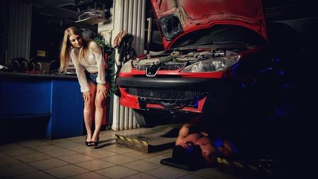 Girl in the garage watching as master man repairs his car Standard-Bild