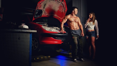 A woman in the garage experiences a sexual attraction to a man with an car mechanic
