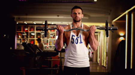 Man athlete with the barbell at the gym