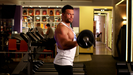 Man athlete with the barbell at the sport gym