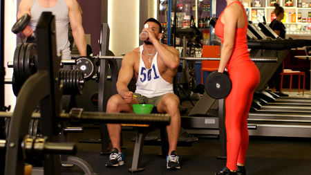 Sports nutrition man eats and drinks in a gym