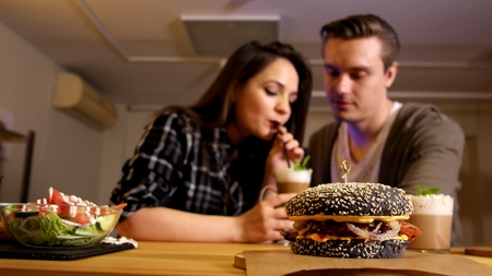 Black burger date man and girl in cafe 스톡 콘텐츠