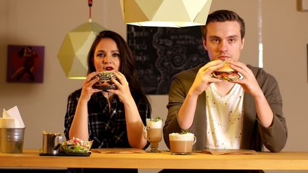 Young couple man and girl on a date to eat burgers