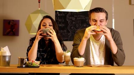 Girl and man bite off black burger 스톡 콘텐츠