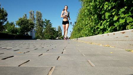 Young girl in the morning sports running in the park Standard-Bild