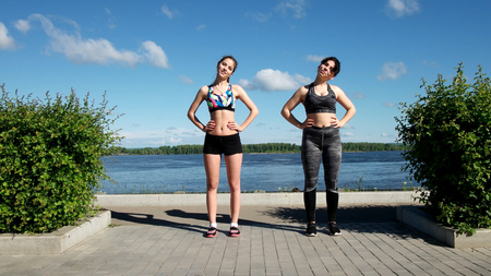 Individual sports trainer girl with a instructor in the park Standard-Bild