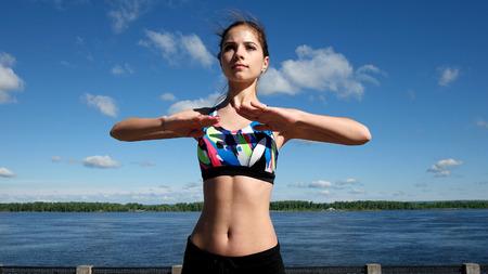 Slender brunette girl and sports embankment quay Standard-Bild