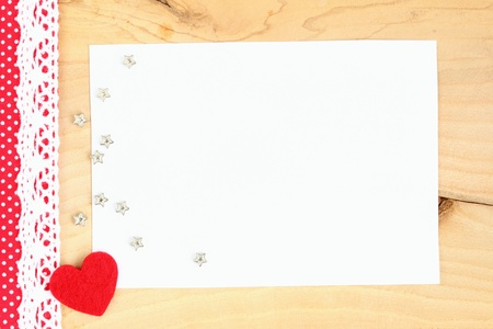 Red heart with braid, several stars and blank space on a wooden background  photo