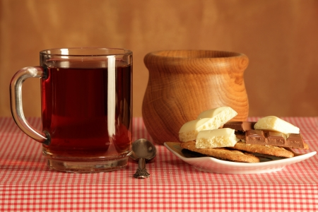 ewer: tea; hot; strong; fresh; glass; transparent; mug; plate; saucer; jug; ewer; wood; background; tablecloth; brown; red; heating; comfort; heat; useful; fragrant; cookies; cereals; spoon; silver; teahouse; chocolate; white; milk; porous;  Stock Photo