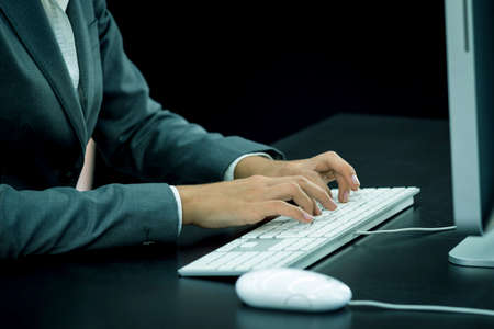 Businesswoman typing at computer