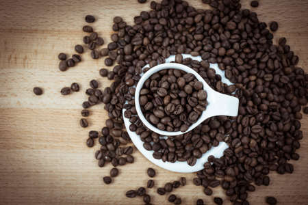 A coffee cup filled with coffee beans and Surrounded by Stock Photo