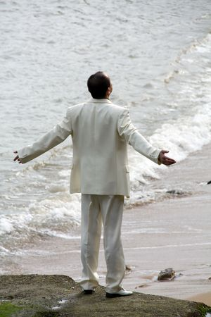 A Chinese groom with arms open at the beach photo